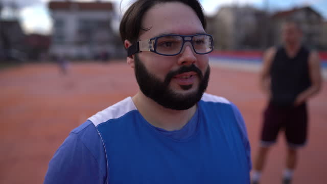 Man putting eyeglasses on basketball court outdoors