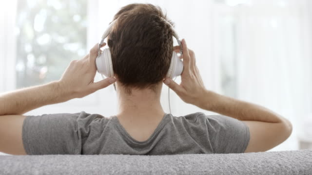 Man putting headphones on his ears Rear view, man putting headphones on his ears headphones stock videos & royalty-free footage
