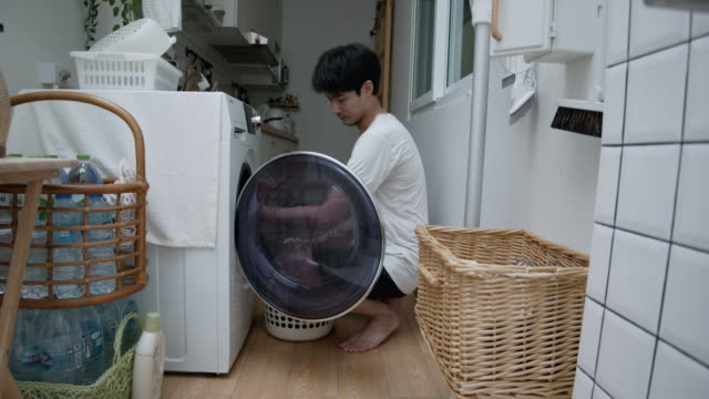 Man Putting Laundry Into Washing Machine Man opens door of washing machine before loading laundry from basket and closing door. laundry basket stock videos & royalty-free footage