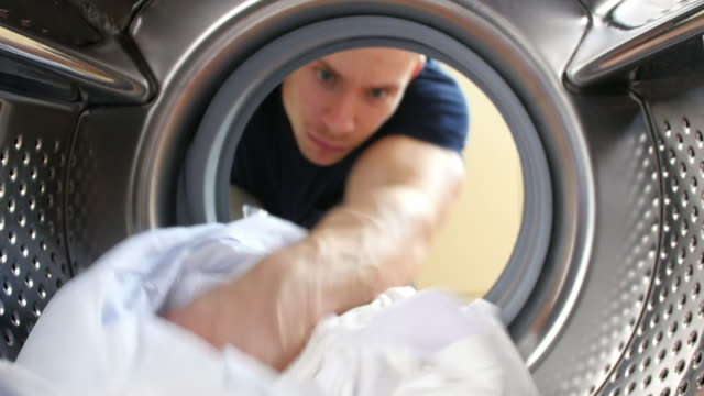 Man Putting Laundry Into Washing Machine video