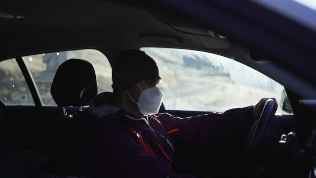 uomo che mette una maschera di salute in un'auto su un passo di montagna in svizzera - abiti pesanti video stock e b–roll