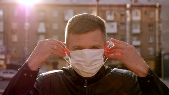 man putting on a protective medical mask and looking to camera. covid-19. - vestirsi video stock e b–roll