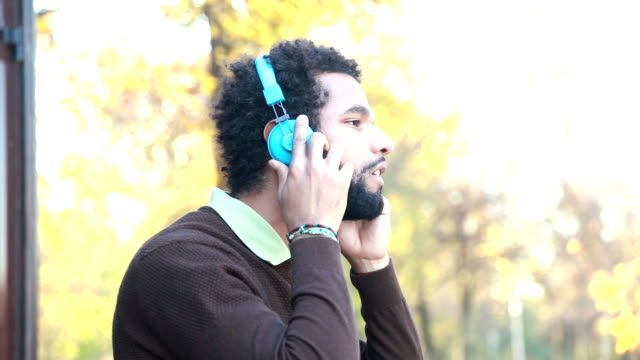 Man putting on headphones and listening to music in nature video