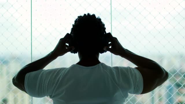 vidéos et rushes de homme mettant sur les écouteurs d'oreilles à la maison écoutant la musique, podcast, ou livre audio, regardant la vue de ville - podcasting