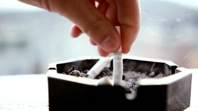 uomo mettendo una sigaretta fumatori in un posacenere con edifici in background - nicotina video stock e b–roll