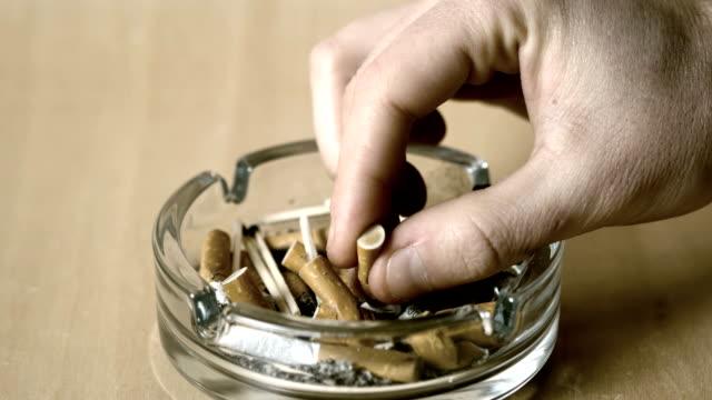 man putting out cigarette in ashtray - nikotin stok videoları ve detay görüntü çekimi