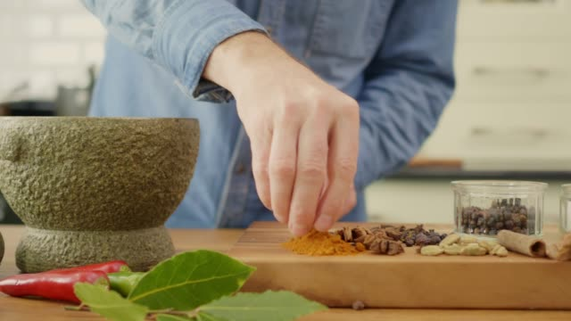 Man Putting Spices Into Stone Mortar And Grinding With Pestle Dolly shot of man putting spices into stone mortar and grinding with pestle. Male is making dry rub seasoning in kitchen. He is cooking food at home. 4K Resolution. mortar and pestle stock videos & royalty-free footage