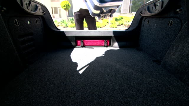 Man putting suitcases in open car trunk video