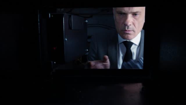 pov man putting us dollars into a safe - avidità video stock e b–roll