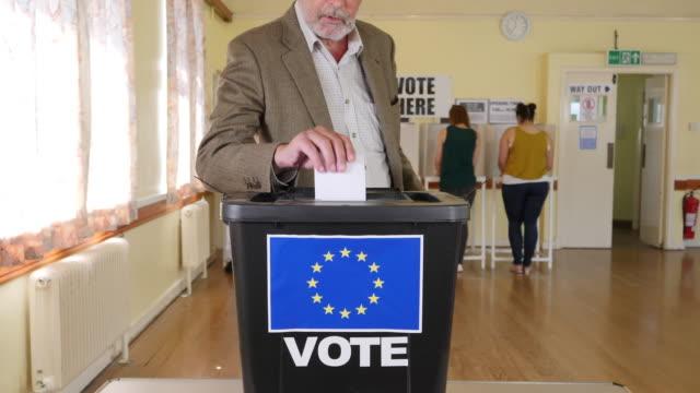 4k: man sätta röst i valurnan på folkomröstningen om eu - utträde - brexit bildbanksvideor och videomaterial från bakom kulisserna