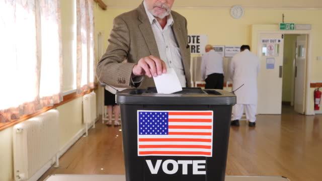 vidéos et rushes de 4k: homme mettant aux voix dans les urnes lors des élections usa - voter au bureau de vote - vote
