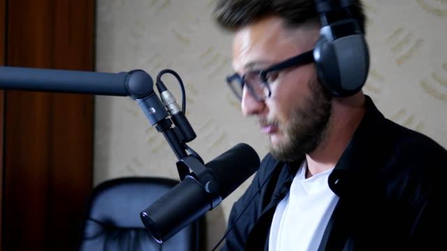man radio host in eyeglasses and headphones says into mike at studio video