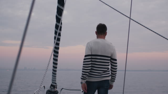 Man raises hands in a relaxing way on a sailboat in the sea. video