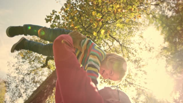 SLO MO Man raising his small laughing child in the air in the sunny park under a tree