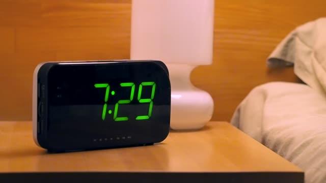 uomo che arriva a spegnere la sveglia digitale al mattino - sonnecchiare video stock e b–roll