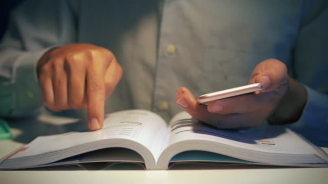 Man reading a book and using smart phone Man reading a book and using smart phone on the floor,Close-Up handbook stock videos & royalty-free footage