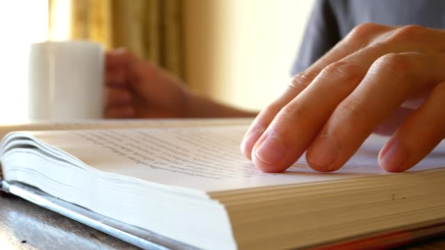 man reading a book, turning pages, and slide his hand to find something - close up view video