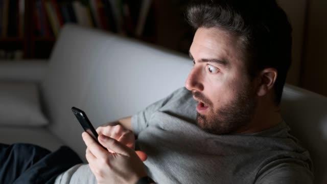 휴대 전화로 메시지를 읽는 남자 - surprise 스톡 비디오 및 b-롤 화면