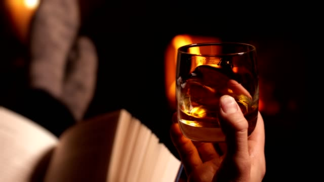man reading book and drinking glass of whisky warming feet by flames of wood burning stove - whisky video stock e b–roll
