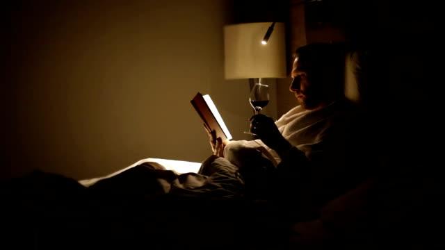 ワインのグラスを楽しむ男読書本 - 赤ワイン点の映像素材/bロール
