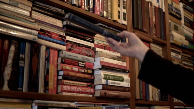 man reading book in front of bookshelf looking and searching