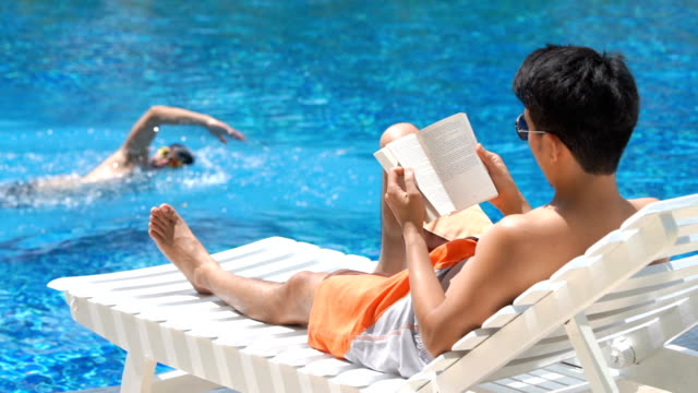 SLO MO Man reading book near swimming pool in summer Asian man in sunglasses reading a book near swimming pool in summer with swimmer background sunbathing stock videos & royalty-free footage