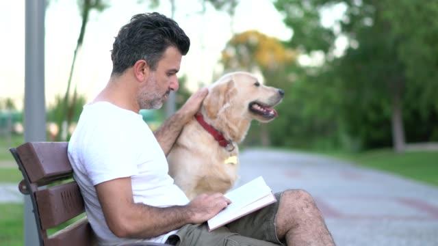stockvideo's en b-roll-footage met man lezen boek met zijn hond op de bank van het park - alleen één mid volwassen man