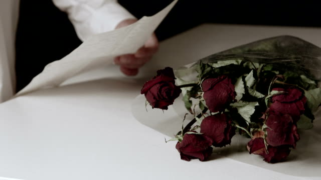 Man reading farewell letter with bouquet of withered roses on table video