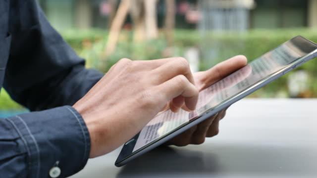 Man Reading text on Digital tablet