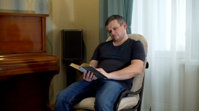 Man Reading the Book on the Rocking Chair Male Reading the Book on the Rocking Chair in his Appartement in the Evening rocking chair stock videos & royalty-free footage