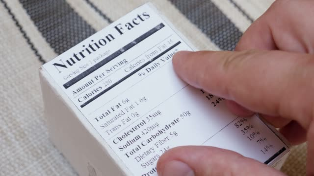 Man Reads Food Labels with Nutrition and Quality