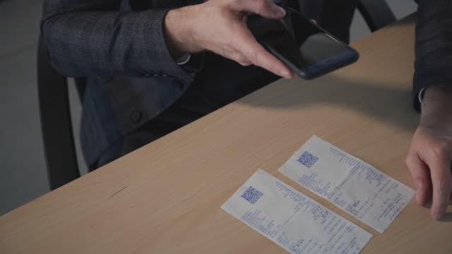男はスマートフォン上のアプリケーションを使用してチェックを読みます。qrコードスキャン - 医療用スキャン点の映像素材/bロール