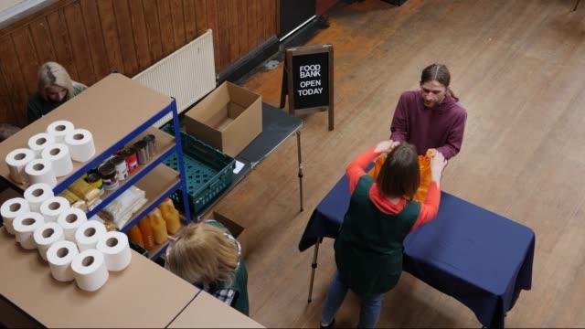 vídeos y material grabado en eventos de stock de 4k antena: hombre recibe la bolsa llena de alimentos / comida en un banco de alimentos - food drive