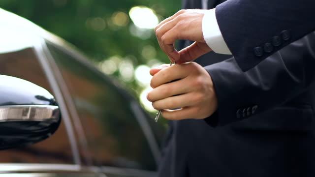 mann erhält schlüssel auf luxus auto händler im salon, probefahrt, nahaufnahme - billionär stock-videos und b-roll-filmmaterial