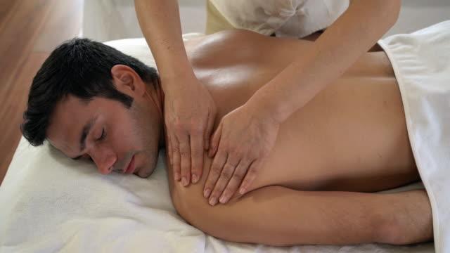 vídeos y material grabado en eventos de stock de hombre recibiendo masaje de cabeza en el spa de belleza - dar masajes