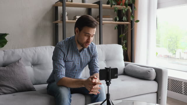 Man recording new video vlog using smart phone Man record videovlog using smart phone seated on couch alone in living room, put device on tripod guy film new vlog make on-line live stream, lead webinar distant chat, modern tech video event concept one man only stock videos & royalty-free footage