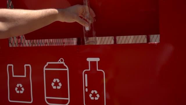 mann recycelt glasflaschen in der recyclingtonne - altglas stock-videos und b-roll-filmmaterial