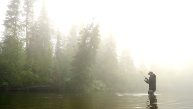Man Reeling in a Fish from a River Enveloped by Fog video