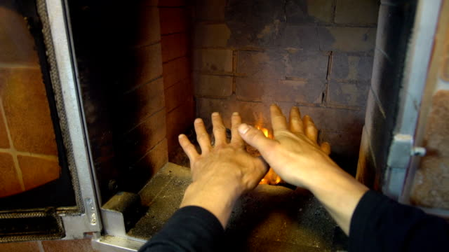 Man relax by warm fire and warming up his hands, nice comfortable fireplace in a house outside the city video
