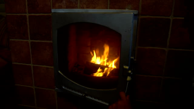 Man relax by warm fire and warming up his hands, open and zoom in, nice comfortable fireplace in a house outside the city video