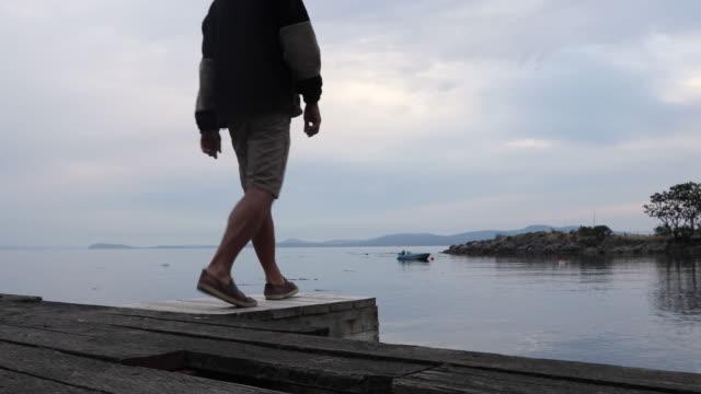 vidéos et rushes de l'homme se détend à la fin du quai de l'océan, temps nuageux - évasion du réel