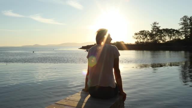 vídeos de stock, filmes e b-roll de homem relaxa no píer com vista para a lagoa das marés, ao nascer do sol - camiseta preta