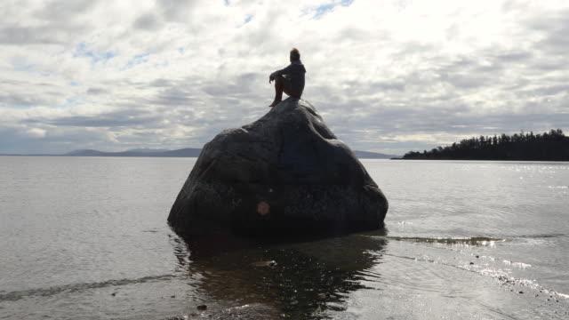 man slappnar av på klippa ovanför grunt hav, vid soluppgången - endast en medelålders man bildbanksvideor och videomaterial från bakom kulisserna