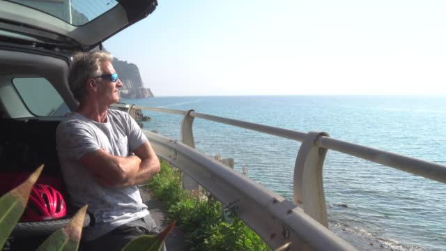 man relaxes with bicycle on car tailgate - спортивное оборудование стоковые видео и кадры b-roll