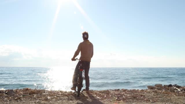 vidéos et rushes de l'homme se détend avec vélo près bord de surf - évasion du réel