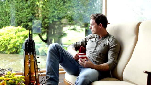 vidéos et rushes de homme se détendre à la maison - thé boisson chaude