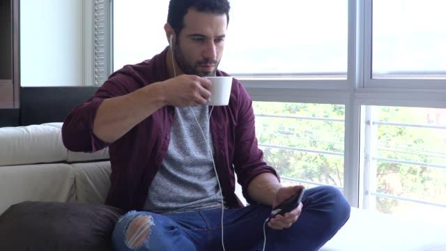 mann entspannend einen kaffee trinken, während man einem podcast zuhört - podcast stock-videos und b-roll-filmmaterial