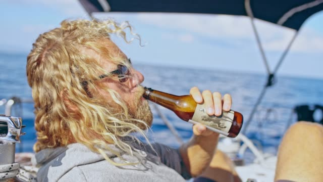 4K Man relaxing, drinking beer on sunny sailboat, real time video