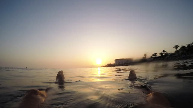 Man relaxing floating in a calm beach at sunset in summer - First person view