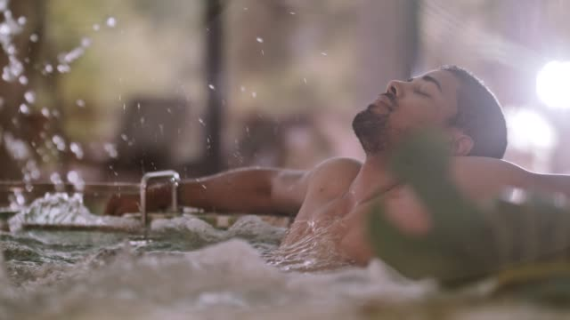 Man relaxing in a hot tub at spa Mixed race man with arms outstretched relaxing in a hot tub at daily spa. Change of focus from a man to foreground view. spa treatment stock videos & royalty-free footage